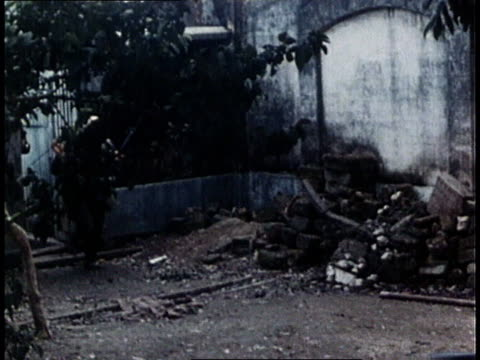 vidéos et rushes de two marines firing small field gun in street / soldiers on foot runing through rubble strewn street / soldiers running in street behind jeep - 1968