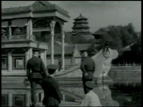 two marines hall of annual prayer building bg ms soldiers on boat in canal drifting towards temple boat structure la ms elaborate pagoda building ms... - 米国海兵隊点の映像素材/bロール