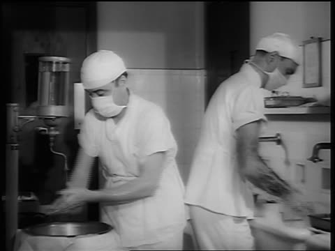 b/w 1948 two masked doctors scrubbing for surgery - scrubbing stock videos & royalty-free footage