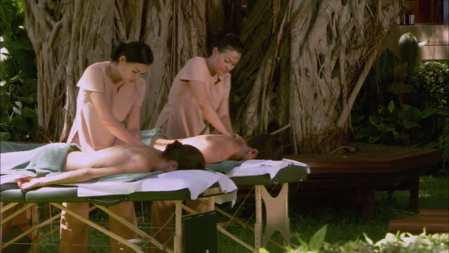 ms pan two massage therapists massaging couple lying face down on massage tables near fig tree / hua hin, thailand - face down stock videos & royalty-free footage