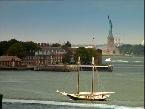 vídeos de stock, filmes e b-roll de two masted brig sails along river statue of liberty in background ellis island new york - porto de nova york