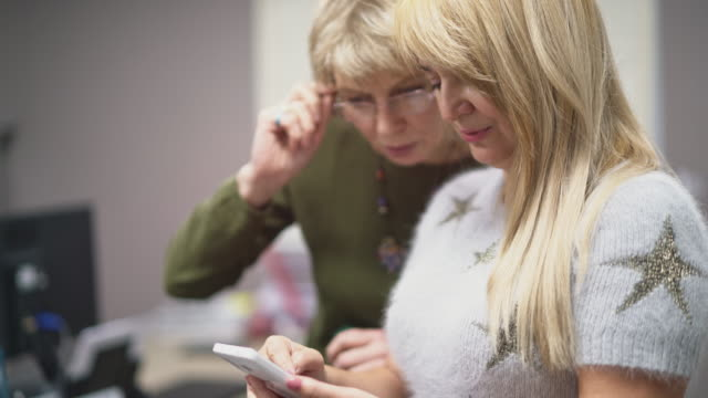 stockvideo's en b-roll-footage met twee volwassen, 50-jarige, zakenvrouwen op zoek naar wat info op het internet met een smartphone - 50 54 years