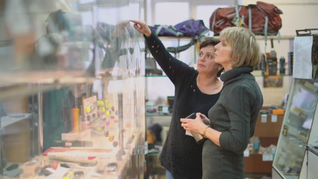 two mature, 50-years-old women looking for purchase in a storefront in a small store. - armeria negozio video stock e b–roll
