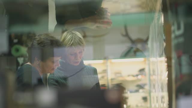 vídeos y material grabado en eventos de stock de dos mujeres maduras, de 50 años de edad que buscan una compra en un escaparate en una pequeña tienda. - 50 54 years