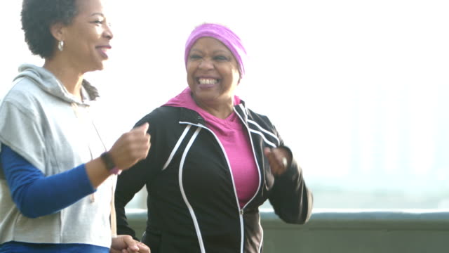 Two mature African-American women exercising in city