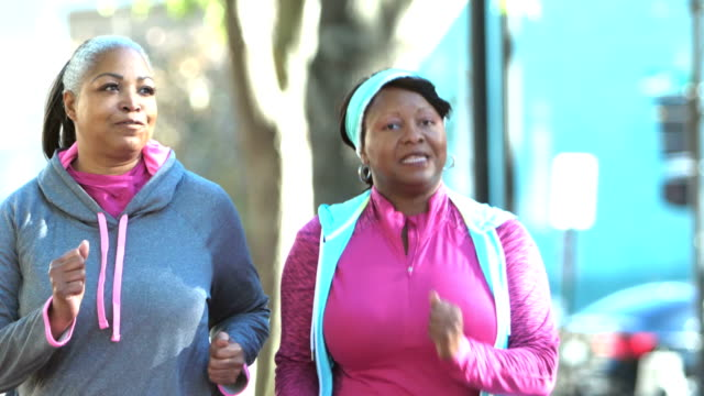 Two mature African-American women power walking in city