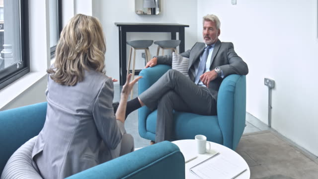 two mature business couple discussing with colleague in modern office - business relationship stock videos and b-roll footage