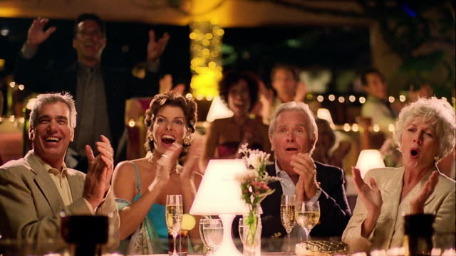 vídeos de stock, filmes e b-roll de ms two mature couples at table watching performance off camera clapping + giving standing ovation - 50 anos
