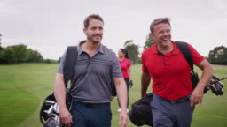 Two Mature Couples Playing Golf Walking Along Fairway Carrying Golf Bag