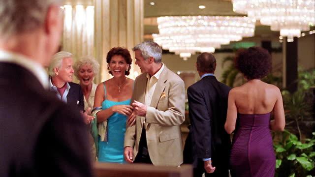vídeos de stock, filmes e b-roll de ms two mature couples walking towards maitre d' of restaurant who shows them to table off camera - de braços dados