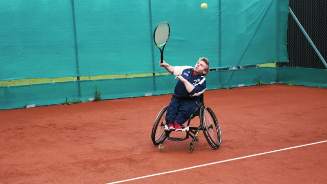 two mature men playing doubles in wheelchair tennis outdoors - disability stock videos & royalty-free footage