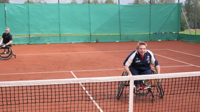 vídeos de stock e filmes b-roll de two mature men playing doubles in wheelchair tennis outdoors - cadeira de rodas