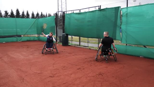 stockvideo's en b-roll-footage met twee rijpe mensen die dubbelen in rolstoeltennis in openlucht spelen - moed