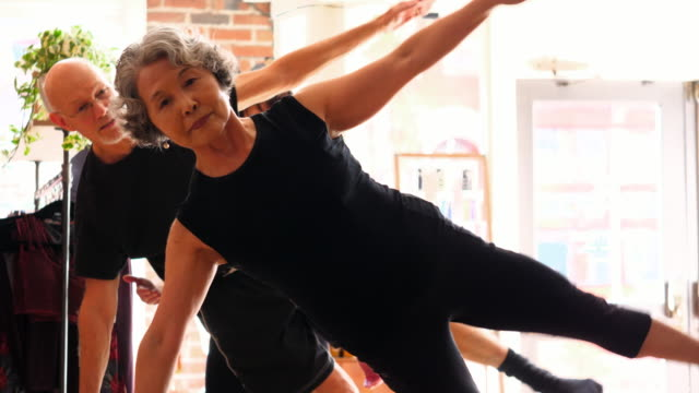 stockvideo's en b-roll-footage met ms two mature pilates students working out on pilates reformer during fitness class - pilates