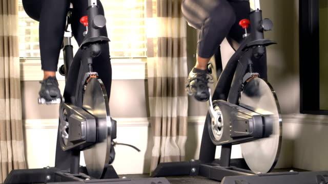 スピニングクラスを取る2人の成熟した女性 - インドアサイクリング点の映像素材/bロール