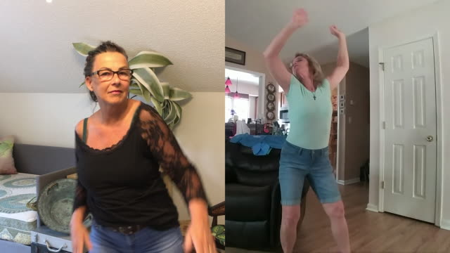 two mature women dance together in their homes while video chatting. - active lifestyle stock videos & royalty-free footage