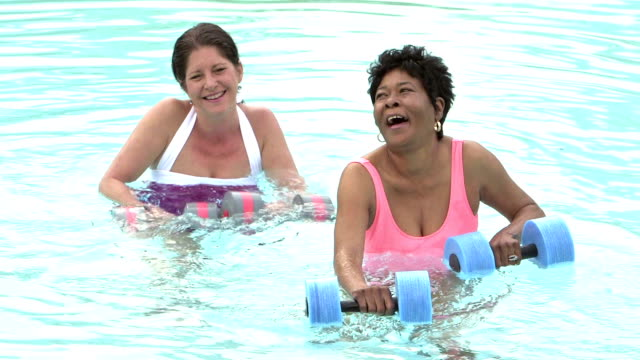 two mature women doing water aerobics - minority groups stock videos and b-roll footage