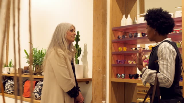 MS Two mature women in discussion while shopping together in boutique