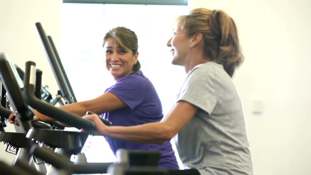 Two mature women talking, working out on exercise bikes