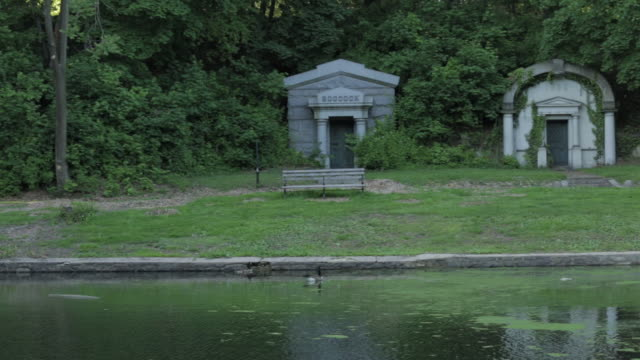 two mausoleums shrouded in trees and weathered bench across moss covered dell water pond. - weathered stock videos & royalty-free footage
