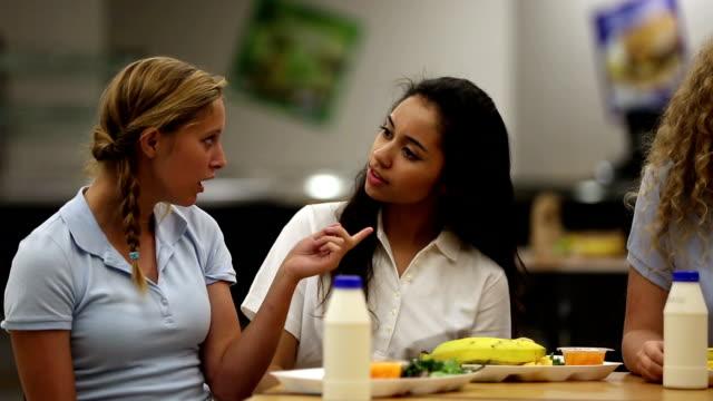Deux jeunes filles parlant signifie Mauvais sur la jeune fille à l'école-cafétéria