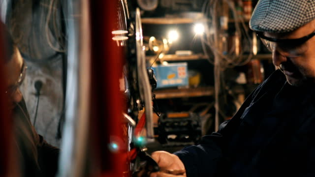 stockvideo's en b-roll-footage met twee monteurs repareren van fietsen in werkplaats - herstel