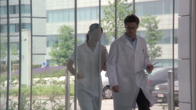 vidéos et rushes de two medical professionals walk into a hospital lobby. - hall d'accueil