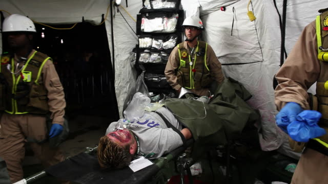 WIDE SHOT two medical workers lift injured man on stretcher in tent - members of US Marines and FDNY take part in joint drill aimed at strenghting preparedness for chemical and biological attacks at Barclays Center