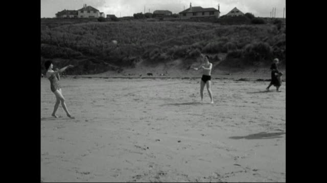 two men and a woman throw ball around on beach;1951 - 1951 stock videos & royalty-free footage