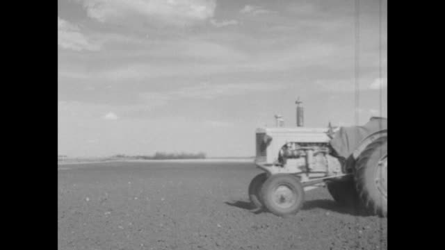 ls two men and dog walk away from camera toward farmhouse / vs farmers on tractors till soil / note exact day not known - saskatchewan stock videos and b-roll footage