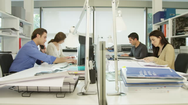 LA WS two men and two women working on  desk in modern office, one man placing phone call