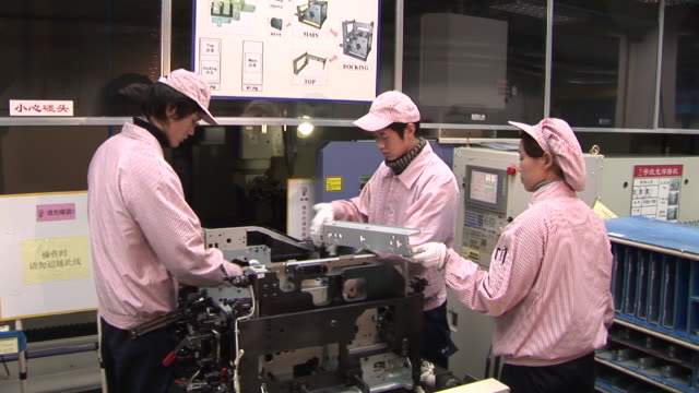 ms two men and woman assembling photocopier in factory/ shanghai, china - occupazione industriale video stock e b–roll