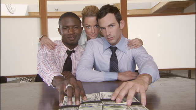 ms, two men and woman sliding stack of cash across table, portrait, los angeles, california, usa - corruption stock videos and b-roll footage
