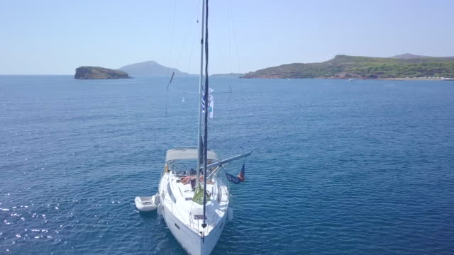 two men and women couples relaxing in hammocks on anchored sailboat aerial drone view near islands in greece. - anchored stock-videos und b-roll-filmmaterial