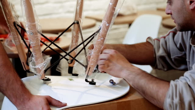 two men are assembling a chair with hands and tools - chair stock videos & royalty-free footage