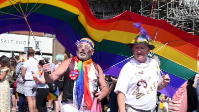 Two men are dressed up and walk under a twoperson umbrella decorated with pride colours and the pride flag in the Gay Pride Parade 2017