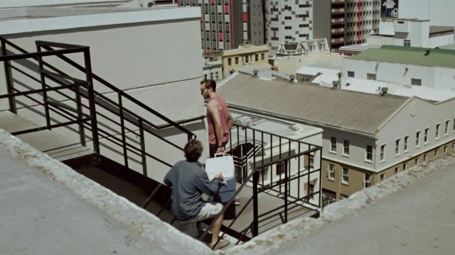zwei männer, die auf der party auf dem dach - kühlbehälter stock-videos und b-roll-filmmaterial