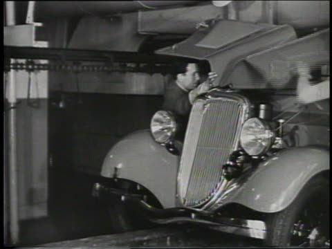 b/w 1932 two men assembling hood of ford car in factory - 1932 stock-videos und b-roll-filmmaterial