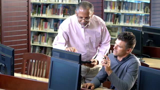 図書館のコンピュータで2人の男 - 公共図書館点の映像素材/bロール