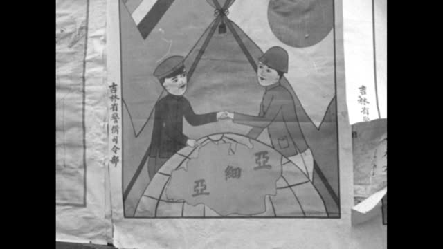 """""""hsinking - flag of new empire is raised: people read propaganda signs in streets; people arrive from out of town; droshkys thru street; mounted... - 天皇点の映像素材/bロール"""