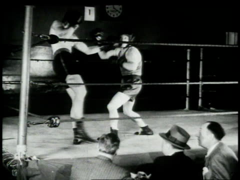 1948 montage two men boxing in ring while cartoonist draws bout / united states - カトゥーニスト点の映像素材/bロール
