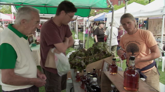 MS Two men buying maple syrup at Farmers Market stall / Rutland, Vermont, USA