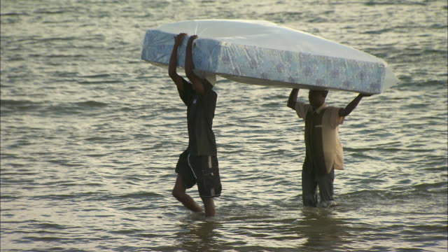 Two men carry a mattress across a shallow river.