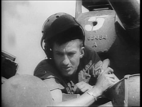 two men carry a wounded soldier / over footage of the marines, damien parer talks about some of the men he met / fighting in jungle, firing artillery... - militärisches landfahrzeug stock-videos und b-roll-filmmaterial