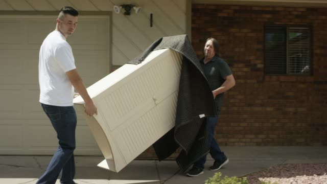 two men carry furniture out to a moving van - physical activity stock videos & royalty-free footage