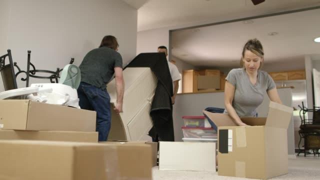 två män bära ut möbler medan en kvinna förpackningar en rörelse rutan - packa bildbanksvideor och videomaterial från bakom kulisserna