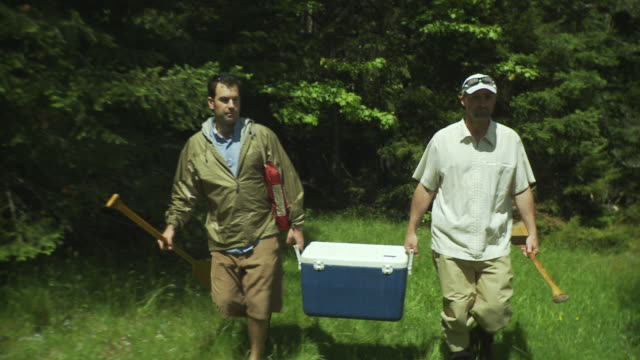 stockvideo's en b-roll-footage met ws shaky two men carrying cooler and canoe paddles to picnic table in lush forest, morristown, vermont, usa - koelbox