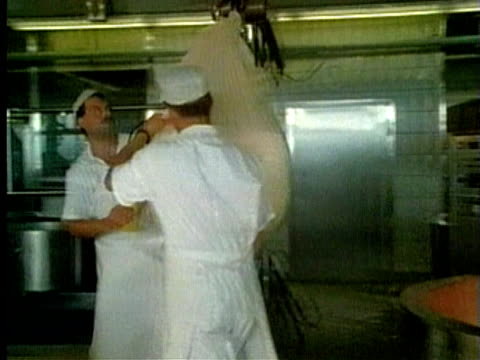 1994 MONTAGE MS PAN Two men carrying large cheese cloth from vat of fermented milk/ MS TU Men pressing down cheese cloth/ AUDIO