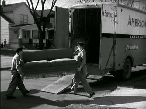 B/W two men carrying sofa onto moving van on suburban street