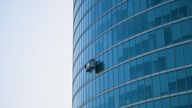 two men clean windows of huge glass business skyscraper in moscow - fönsterrad bildbanksvideor och videomaterial från bakom kulisserna